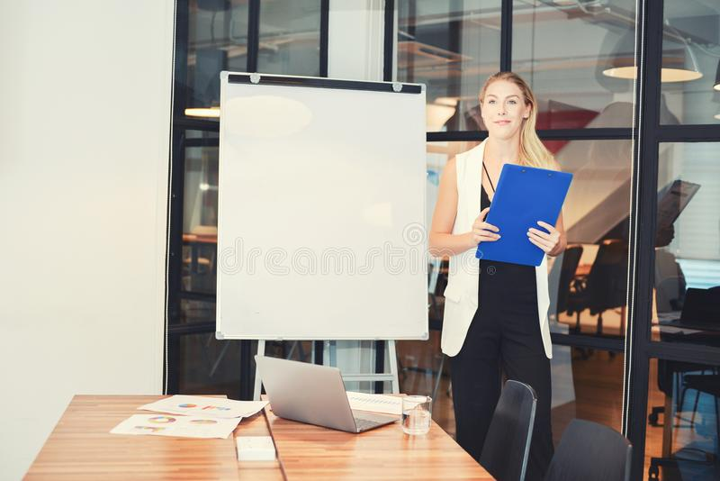 Business blonde woman presenting a project on blank whiteboard stock photo