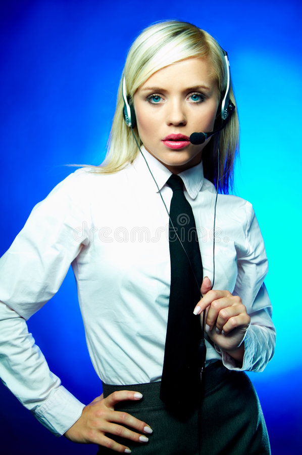 Business on blue. Young Business woman wearing white shirt and black tie with headset working as Call Center Agent royalty free stock photo