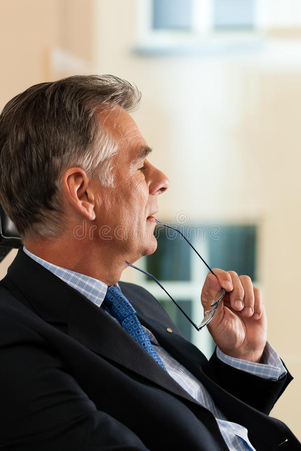 Business - Boss contemplating in his office. Business - mature boss contemplating in his office; he is looking out of the window royalty free stock image