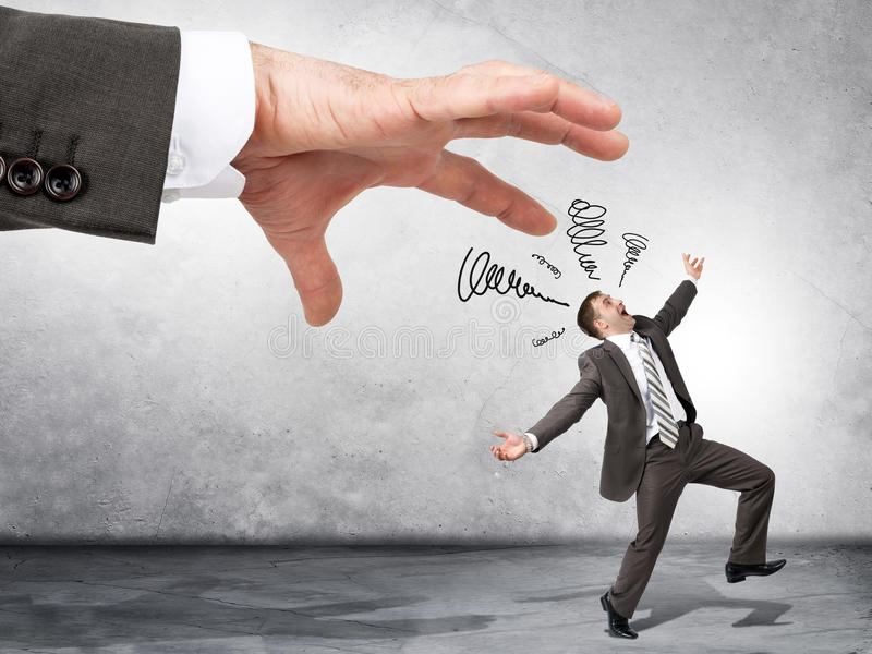 Business boss hand catching scared employee royalty free stock image
