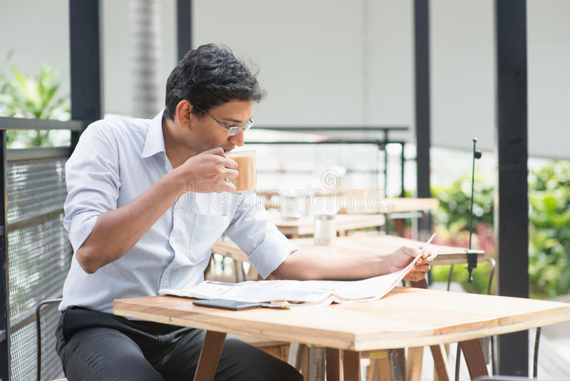 Business break. Asian Indian business man reading newspaper while drinking a cup hot milk tea during lunch hour at cafeteria stock photo
