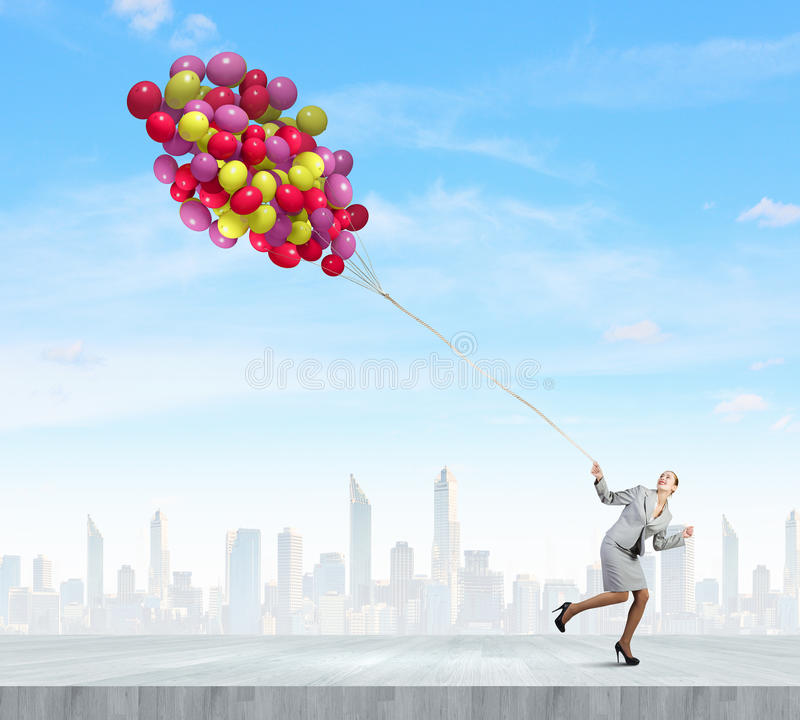 Business break. Young businesswoman running with bunch of colorful balloons stock photo