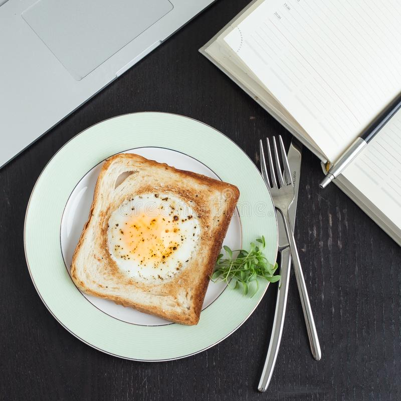 Business breakfast. Egg fried in toast with coffee. Laptop and notebook royalty free stock images