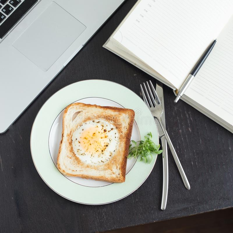 Business breakfast. Egg fried in toast with coffee. Laptop and notebook royalty free stock photo