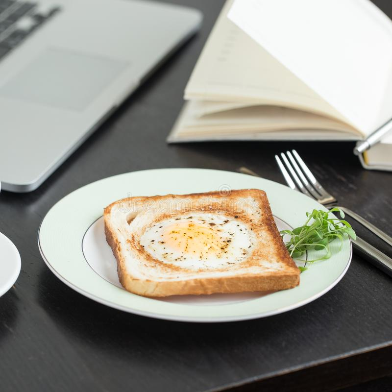 Business breakfast. Egg fried in toast with coffee. Laptop and notebook stock photo