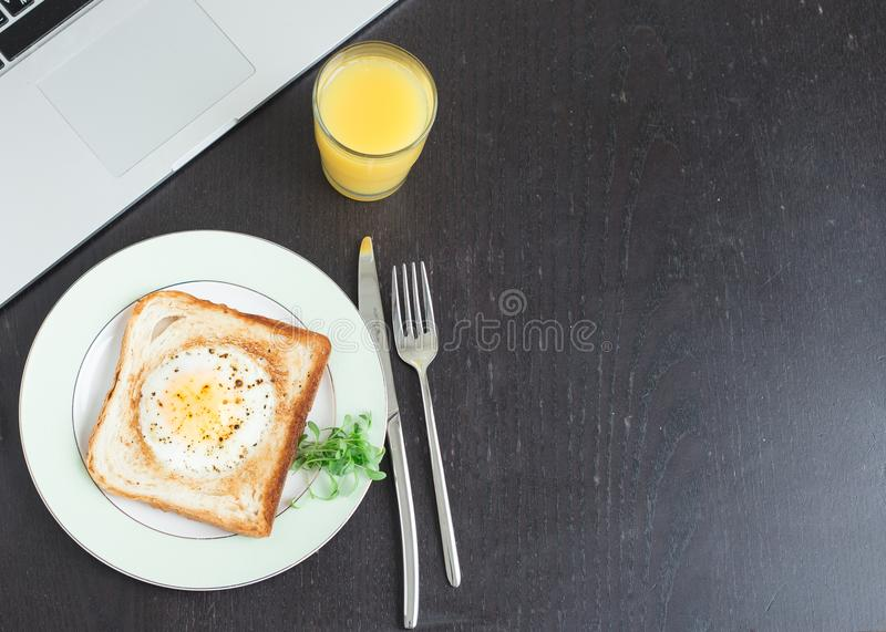 Business breakfast. Egg fried in toast with orange juice. Laptop and notebook stock photos