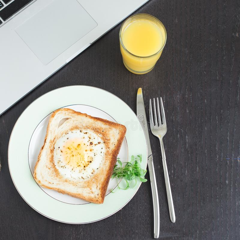 Business breakfast. Egg fried in toast with orange juice. Laptop and notebook stock photography