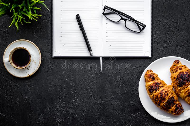 Business breakfast. Small cup of coffee and croissants on office desk. Black background top view copyspace. Business breakfast. Small cup of coffee and royalty free stock photo