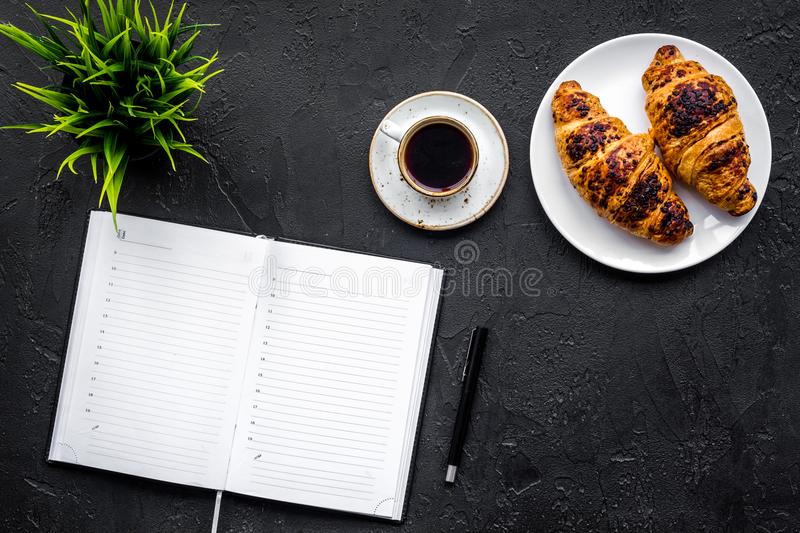 Business breakfast. Small cup of coffee and croissants on office desk. Black background top view copyspace. Business breakfast. Small cup of coffee and stock photography