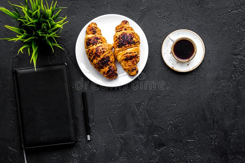 Business breakfast. Small cup of coffee and croissants on office desk. Black background top view copyspace. Business breakfast. Small cup of coffee and royalty free stock photography