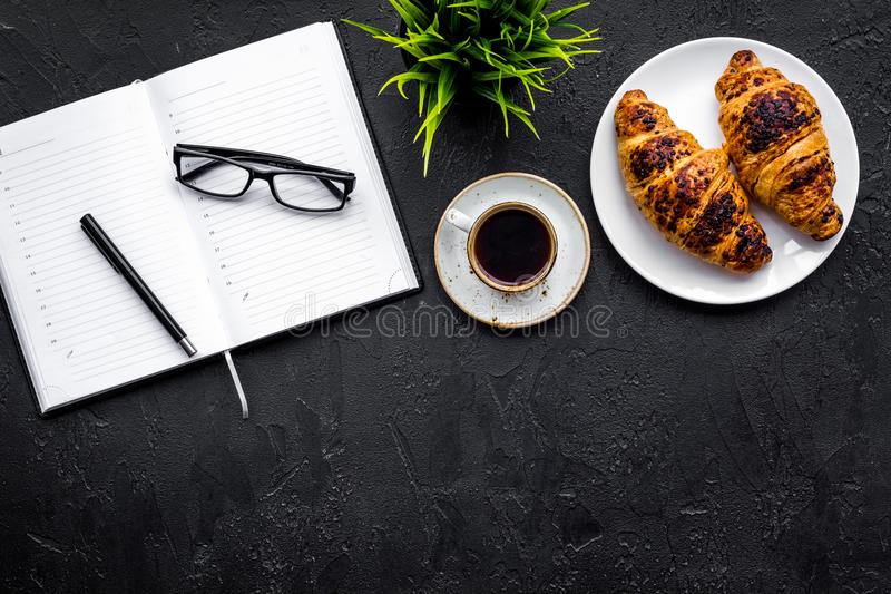 Business breakfast. Small cup of coffee and croissants on office desk. Black background top view copy space. Business breakfast. Small cup of coffee and royalty free stock image