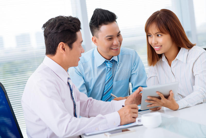 Business briefing. Vietnamese colleagues using digital tablet at the business meeting stock image