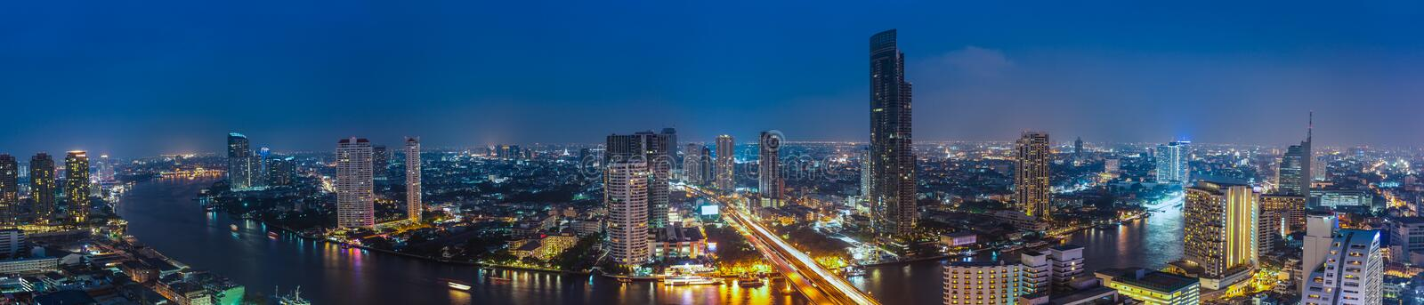 Business Building Bangkok city area at night life with transport. Ation car and ship as panorama, high angle bird eyes view stock photo