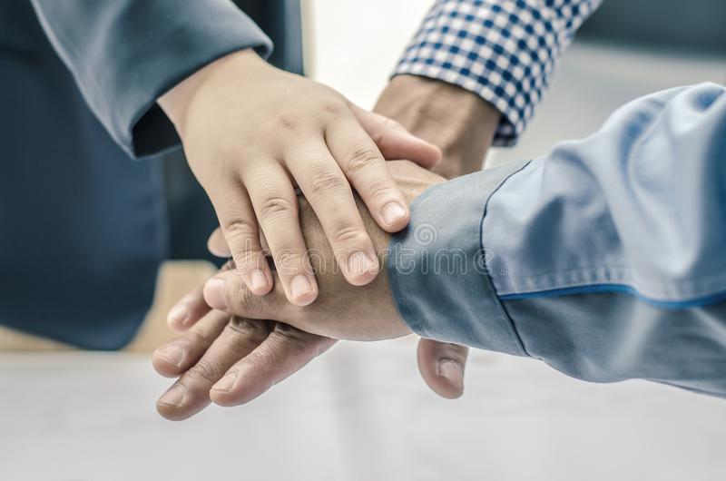 Business, building, partnership, gesture , stacking hands express their teamwork and cooperation stock photography