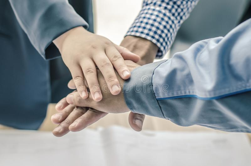 Business, building, partnership, gesture , stacking hands express their teamwork and cooperation stock images