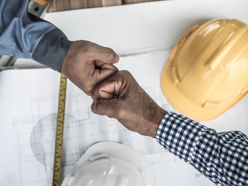 Business, building, teamwork, gesture and people concept - group of smiling builders in hardhats greeting each other with Hand royalty free stock image