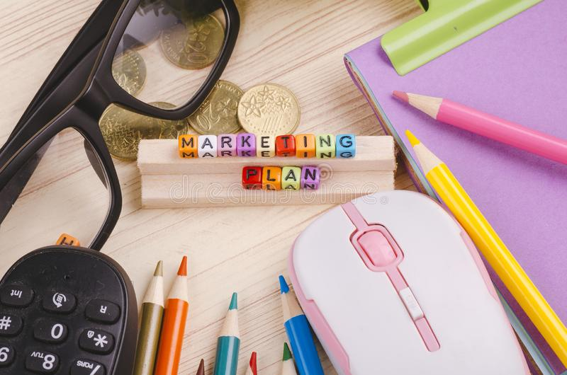 Colorful cube with word MARKETING PLAN on wooden desk stock image
