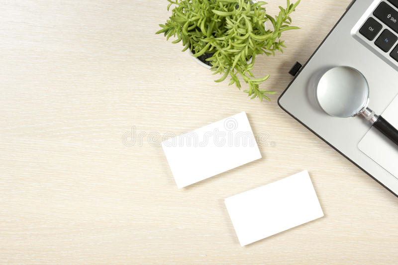 Business card blank, laptop, flower and magnifying glass at office desk table top view. Corporate stationery branding. Mock-up royalty free stock photo