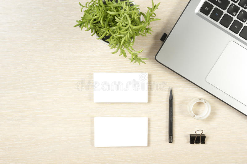 Business card blank, laptop, flower and pencil at office desk table top view. Corporate stationery branding mock-up.  stock photography