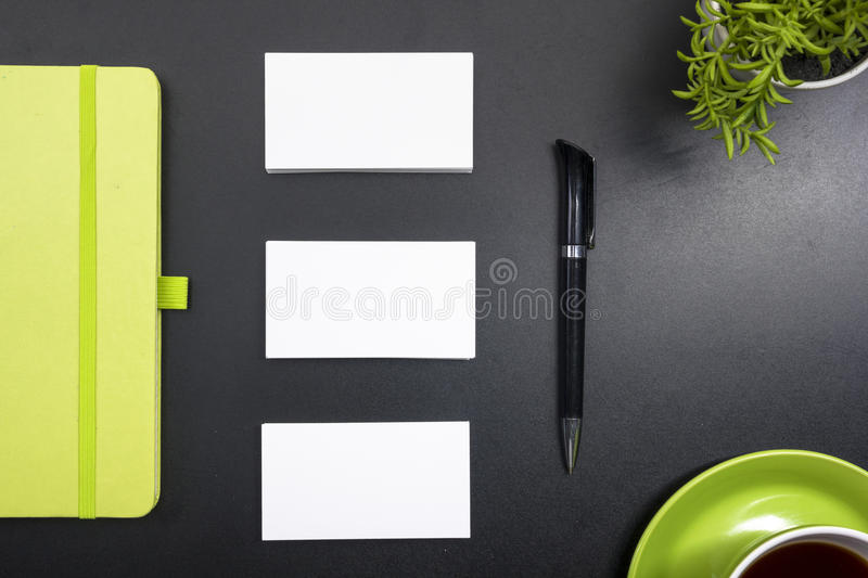Business card blank, notepad, coffee cup and pen, flower at office desk table top view. Corporate stationery branding. Mock-up royalty free stock photography