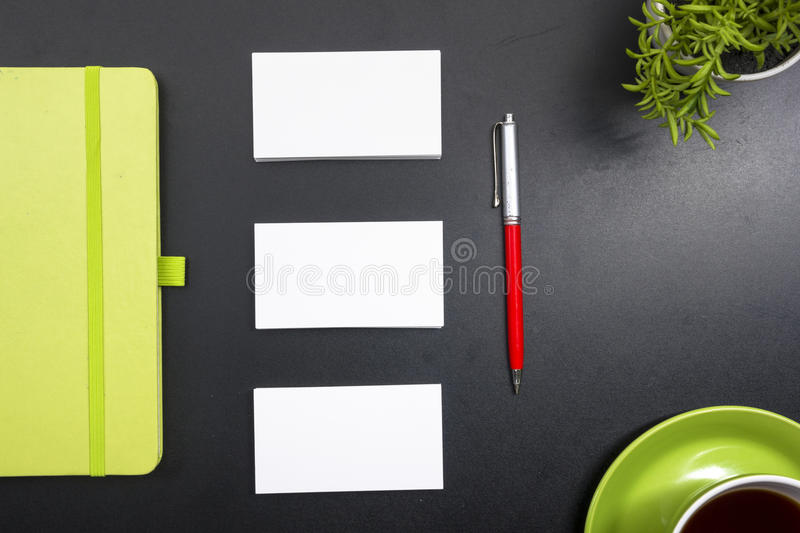 Business card blank, notepad, coffee cup and pen, flower at office desk table top view. Corporate stationery branding. Mock-up royalty free stock photo