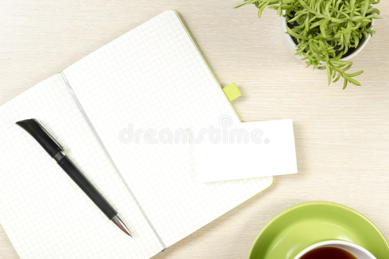 Business card blank, notepad, coffee cup and pen, flower at office desk table top view. Corporate stationery branding royalty free stock photos