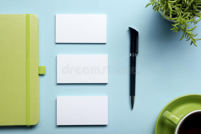 Business card blank, notepad, flower, coffee cup and pen at office desk table top view. Corporate stationery branding royalty free stock photos