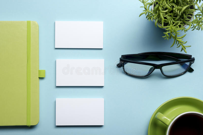 Business card blank, notepad, flower, coffee cup and pen at office desk table top view. Corporate stationery branding royalty free stock photo