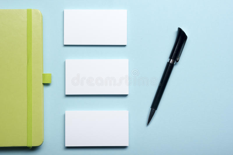 Business card blank, notepad, flower, coffee cup and pen at office desk table top view. Corporate stationery branding royalty free stock images