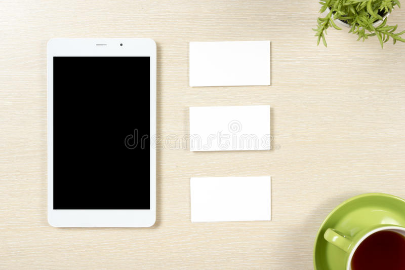 Business card blank, smartphone or tablet pc, flower and coffee cup at office desk table top view. Corporate stationery. Branding mock-up royalty free stock image