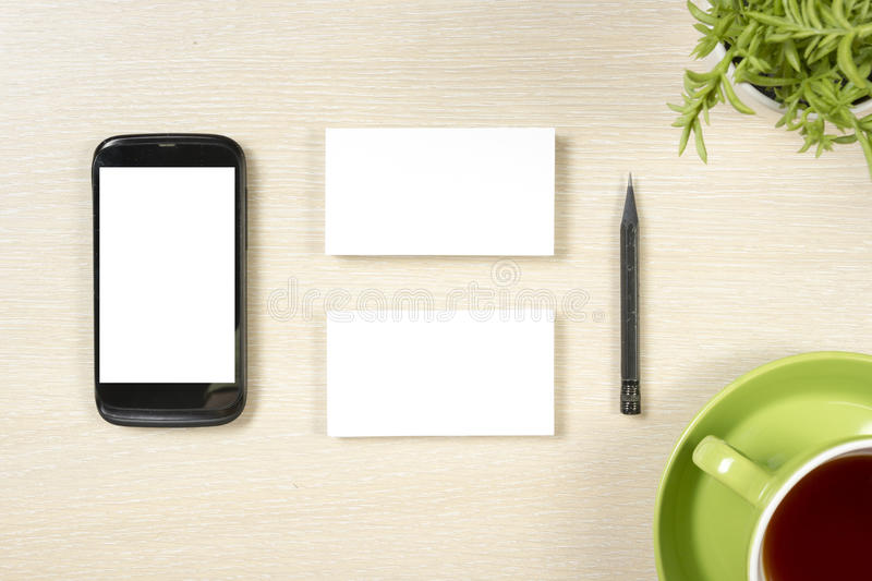 Business card blank, smartphone or tablet pc, flower, coffee cup and pencil at office desk table top view. Corporate royalty free stock photo