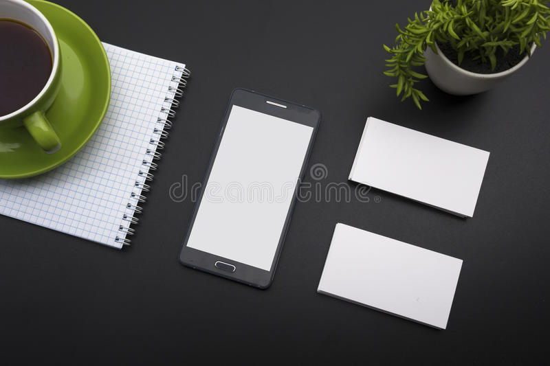 Business card blank, smartphone or tablet pc, flower and pen at office desk table top view. Corporate stationery royalty free stock image