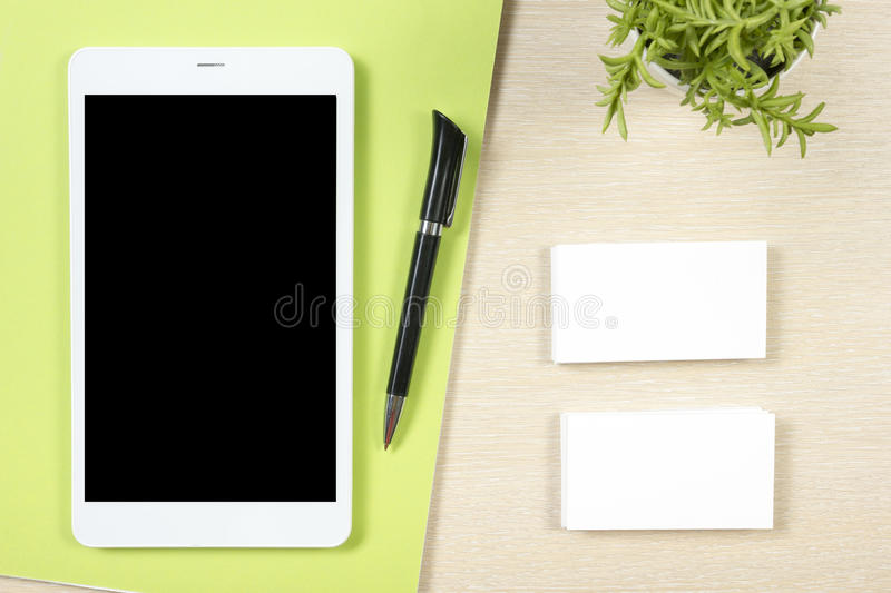 Business card blank, smartphone or tablet pc, flower and pen at office desk table top view. Corporate stationery. Branding mock-up royalty free stock images
