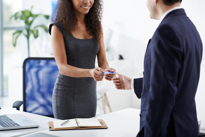 Business card. Female entrepreneur giving business card to client stock photography