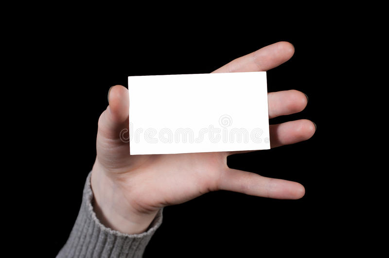 Business card in the hand. On a black background stock image