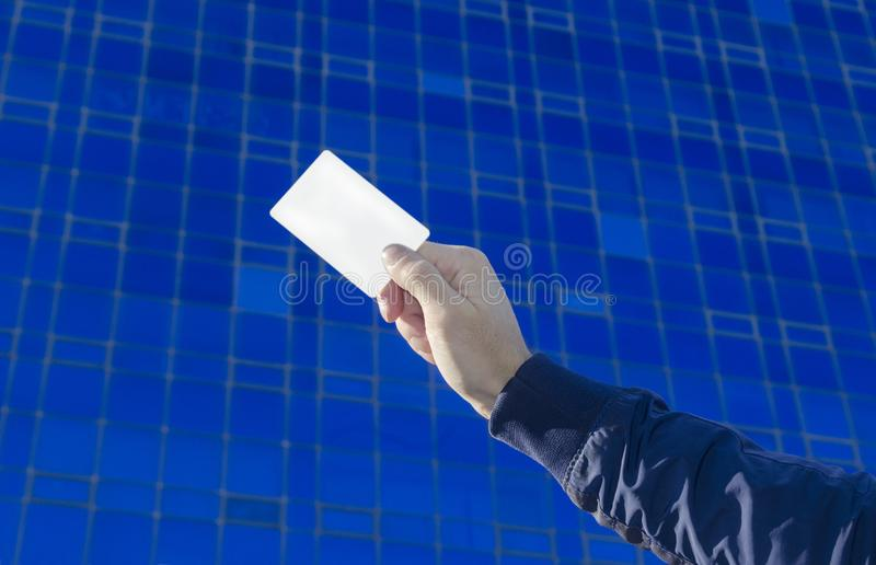 Business card in hand. White Business card in man hand on blue background royalty free stock image