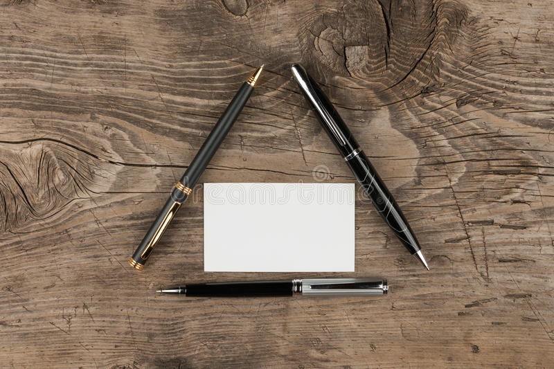 Business card and three ballpoint pens lying on the wood in the shape of a triangle stock photos