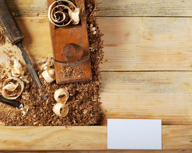 Business card on wooden table for carpenter tools with sawdust. stock image