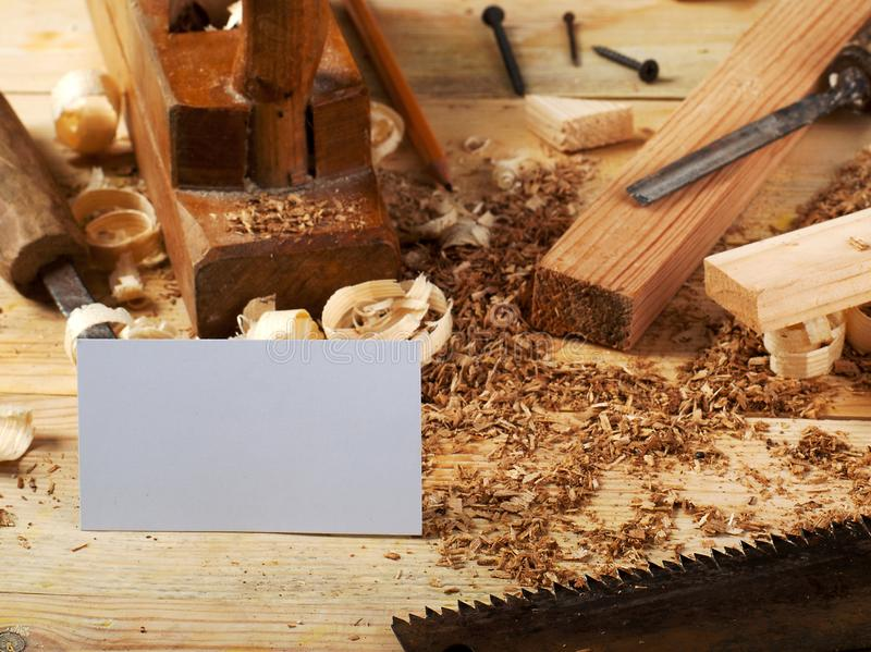 Business card on wooden table for carpenter tools with sawdust. royalty free stock photography