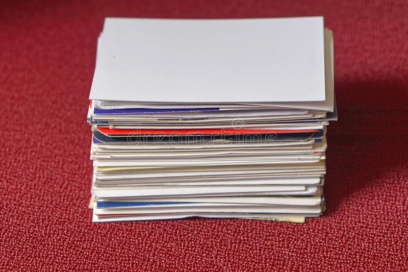 Business cards. Big stack of business cards at red table stock photo