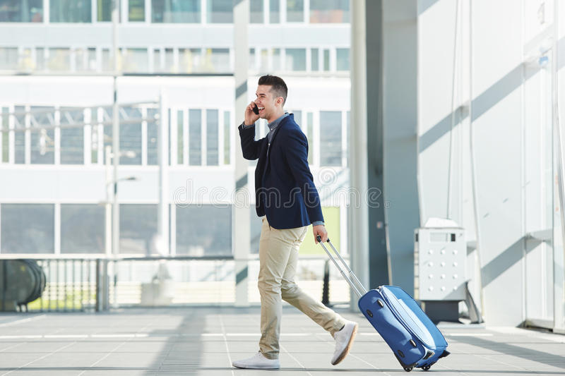 Business casual man walking in station with phone and suitcase. Full length side portrait of business casual man walking in station with phone and suitcase royalty free stock images