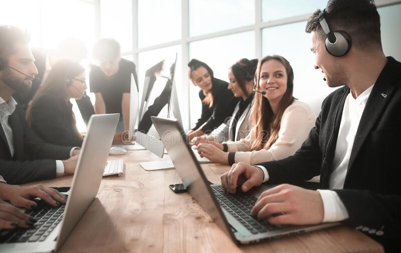 Business center employees using computers in the workplace stock image