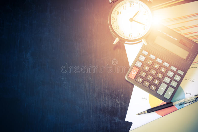 Business chart analysis report with pen, calculator and alarm cl. Ock on office table. Business background concept. Soft light and vintage filtered royalty free stock photos