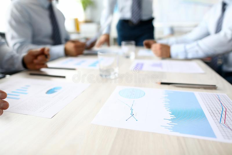 Business chart lie on table against group people stock image
