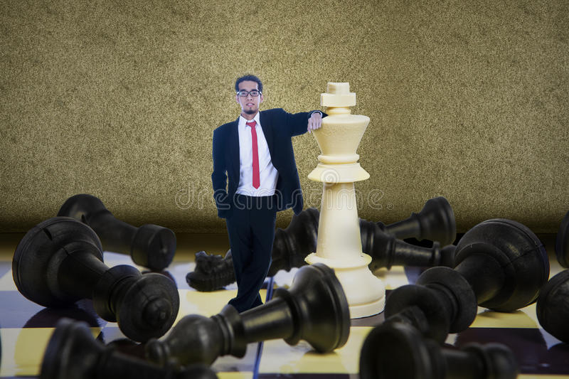 Business checkmate. Businessman winning chess game on brown background royalty free stock photography