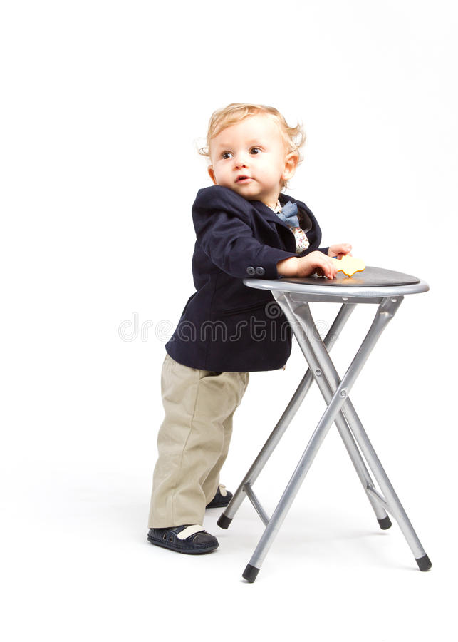 Business child. Office child dressed in business outfit next to a small chair royalty free stock photos