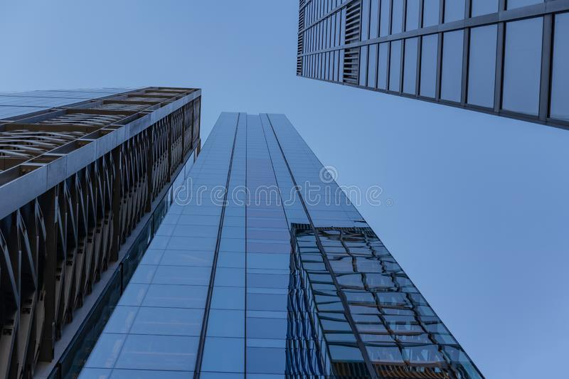 Business circle office buildings at a bright sunny day on the blue sky background. Economy finances and business activity concept. Low angle view stock photo
