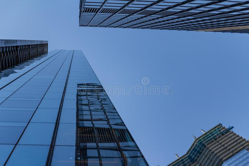 Business circle office buildings at a bright sunny day on the blue sky background. Economy finances and business activity concept. Low angle view royalty free stock photography