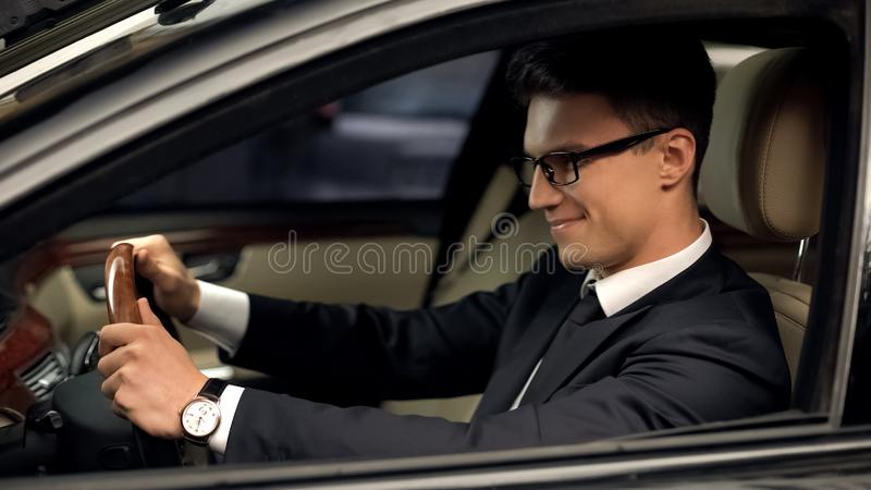 Business class driver sitting in car, satisfied with new job, expensive auto. Stock photo stock image