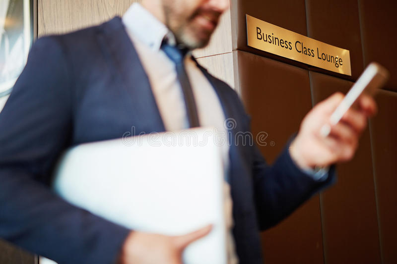 Business class lounge. Businessman at airport in business class lounge royalty free stock photography